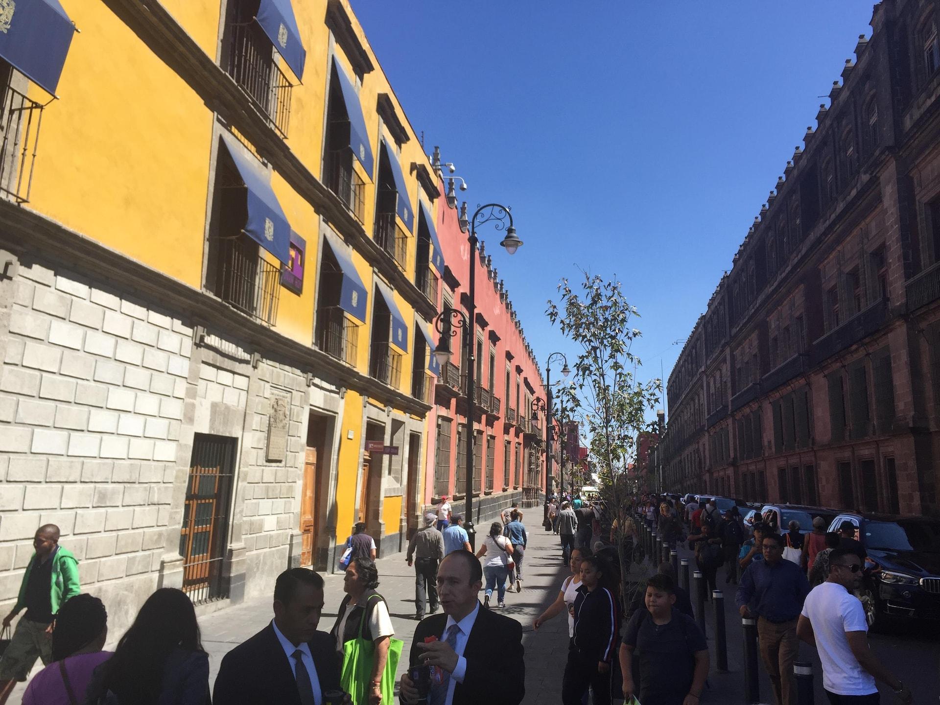 Des passants dans une rue bordée d'immeubles.