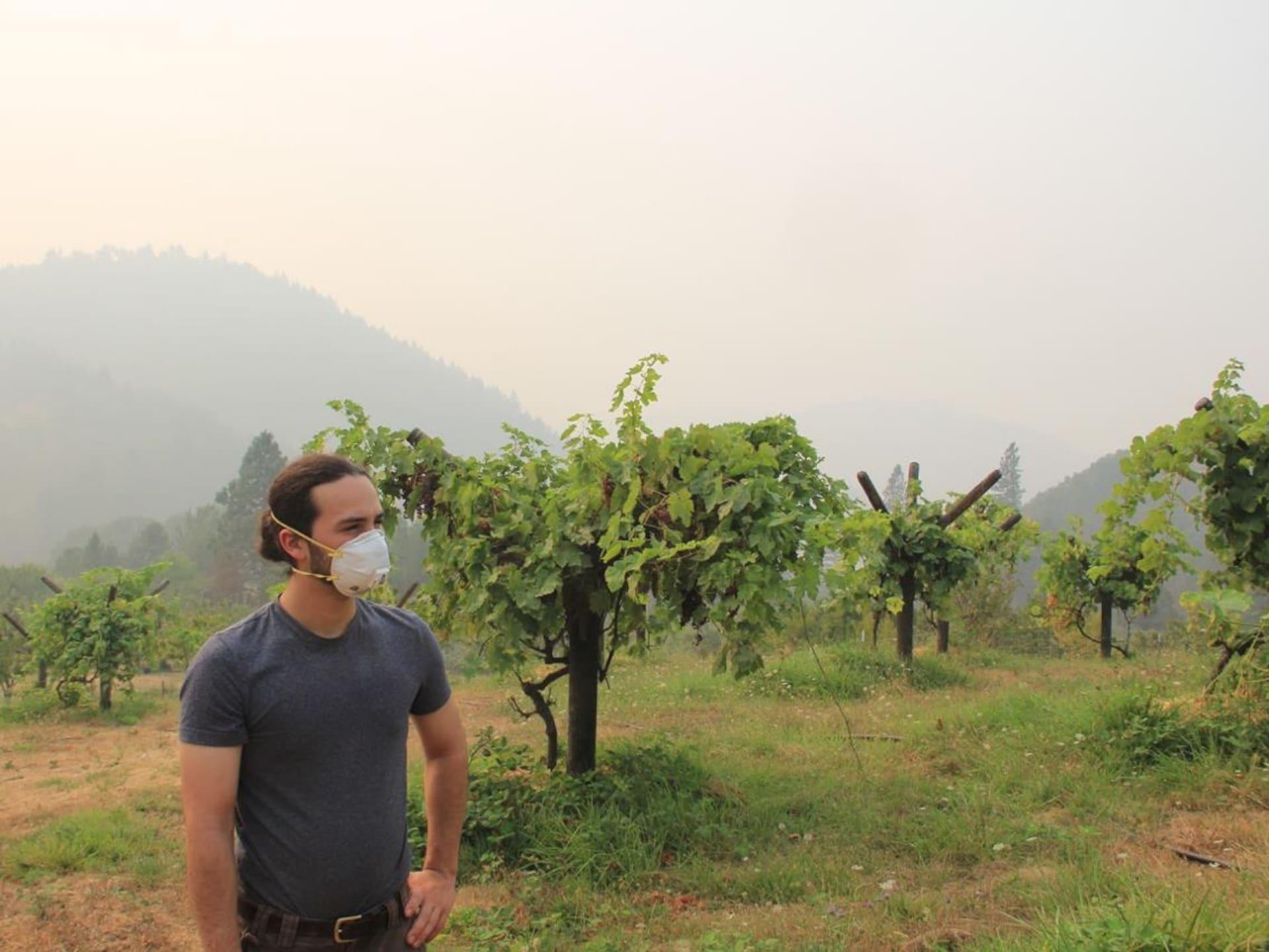 Jacob Lebel, debout dans un champ enfumé, porte un masque.