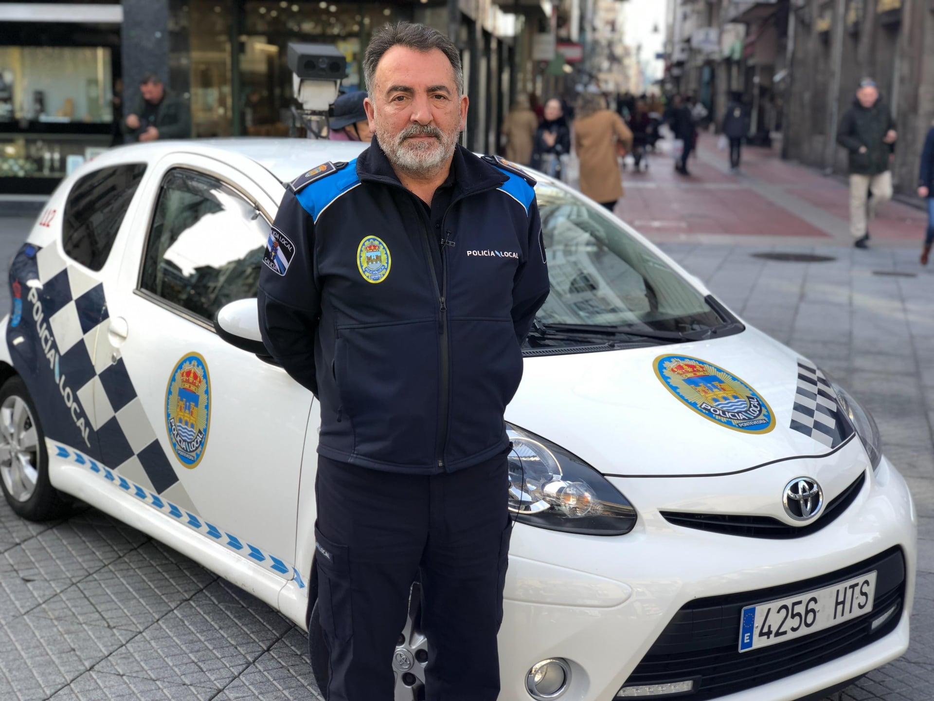 Un policier devant sa voiture.