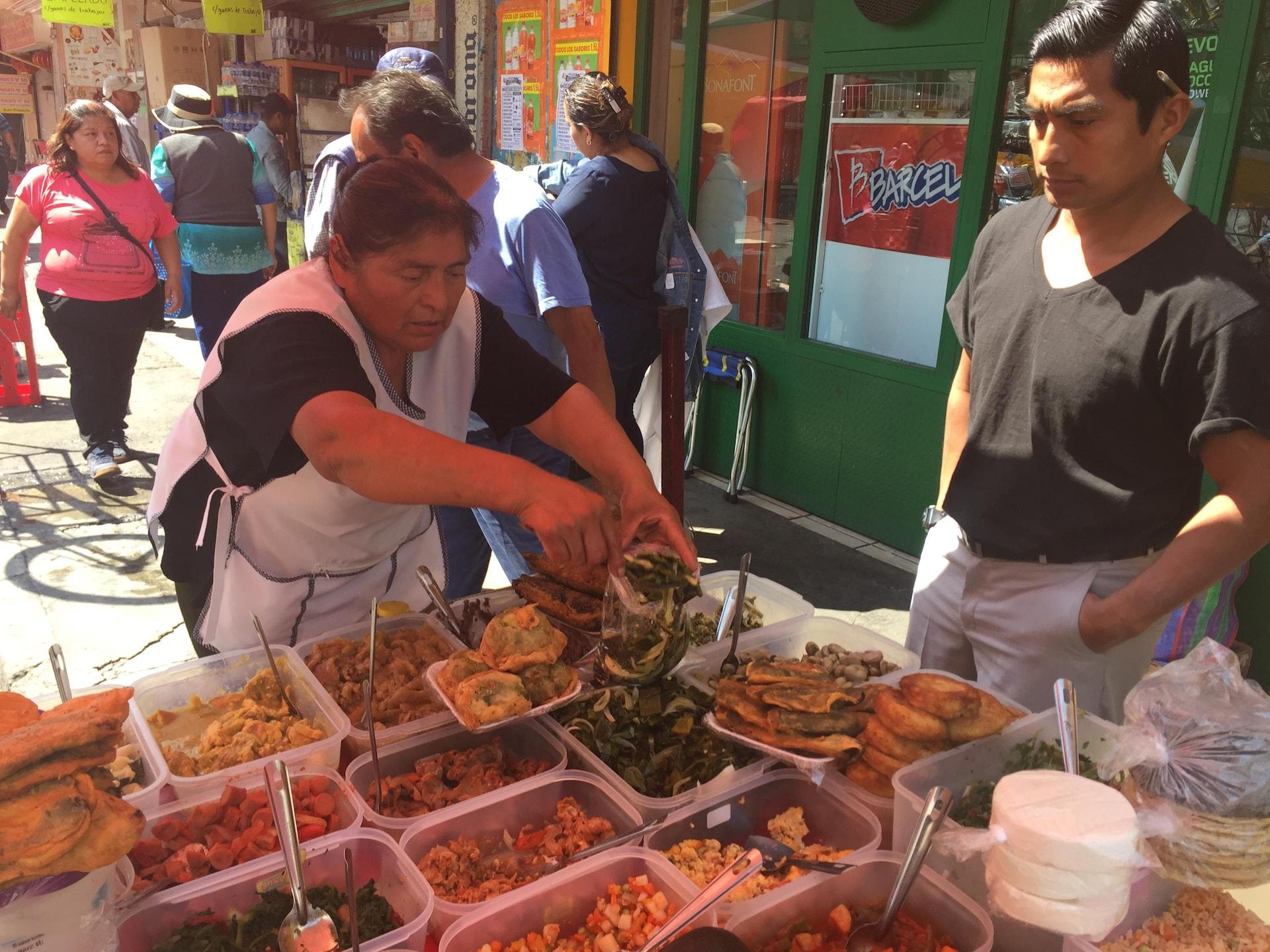 Une marchande sert à manger à un passant.
