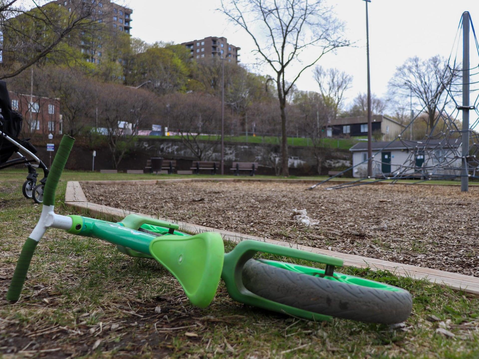 Un vélo abandonné le long d'une aire de jeu, dans un parc. L'endroit est désert et la journée nuageuse. On ne voit aucun enfant à l'horizon. On voit aussi les roues d'une poussette stationnée à côté.