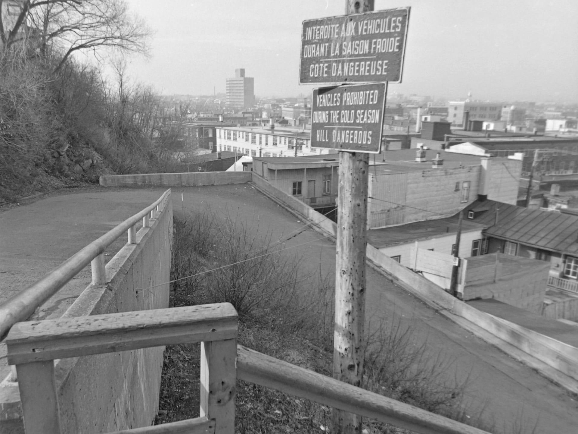 Un virage en épingle dans une côte escarpée, vue d'un escalier situé à côté. Un panneau précise que le passage est interdit aux voitures durant la saison froide.