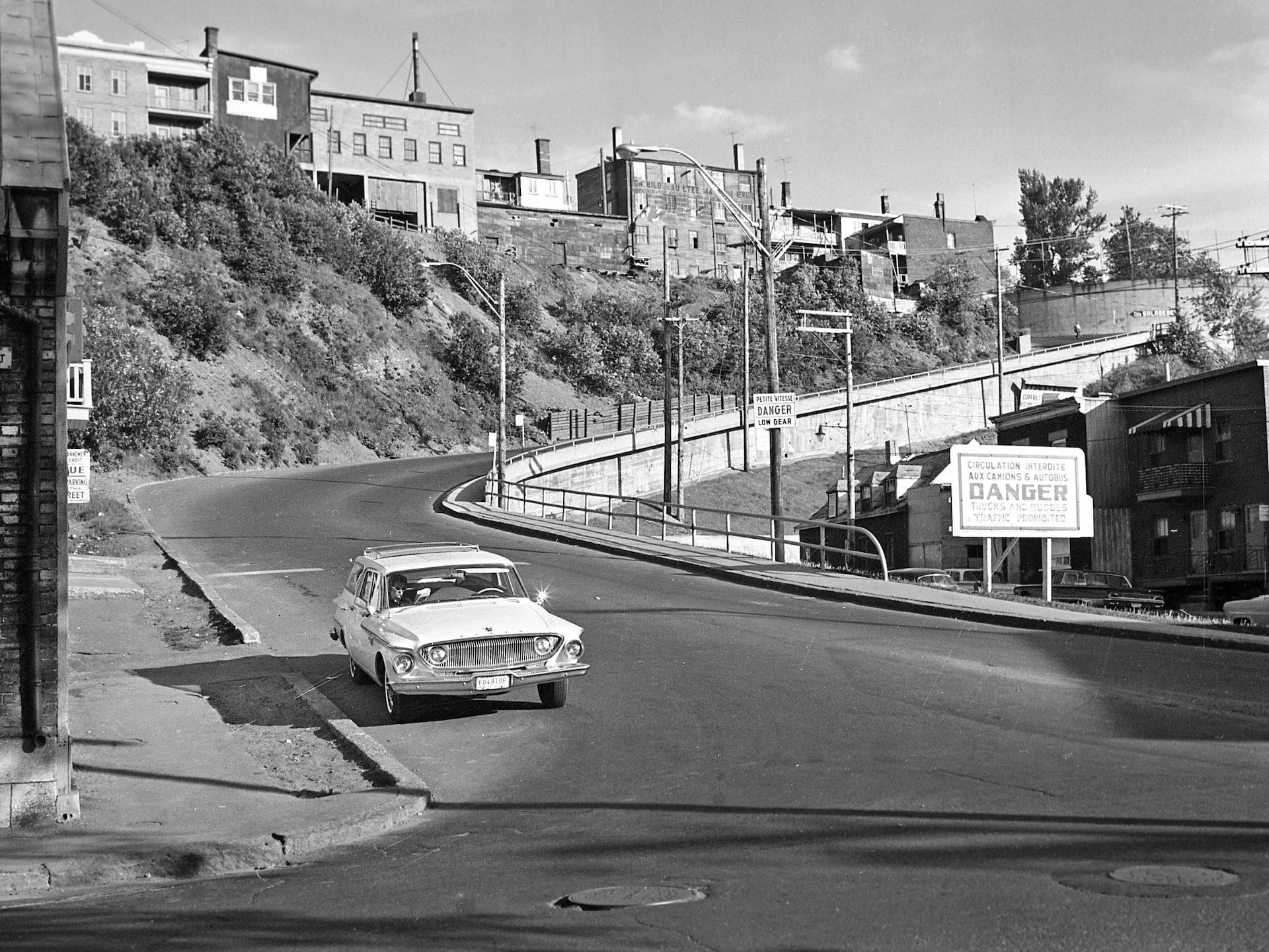 Une voiture solitaire prend le virage en bas de la côte Salaberry, par une journée ensoleillée d'été, La photo remonte aux années 1960. Un panneau bien visible précise que les camions et les autobus ne peuvent pas y circuler.
