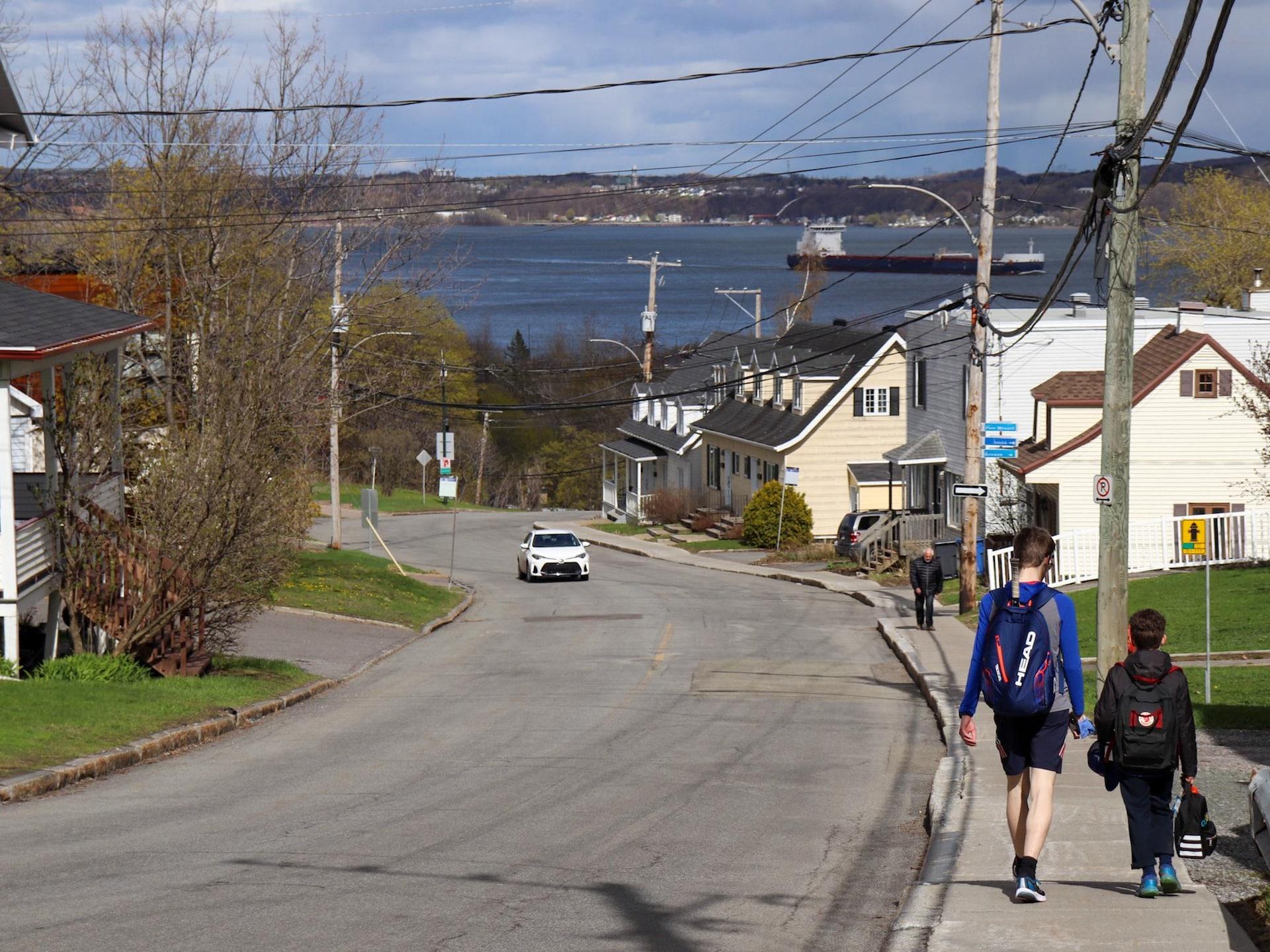 Deux enfants marchent le long d'une côte. Ils portent des sacs de sports. On voit un homme monter au loin et une voiture. Il fait beau, et le fleuve s'étale à perte de vue en bas, avec un bateau-conteneur filant vers l'ouest.