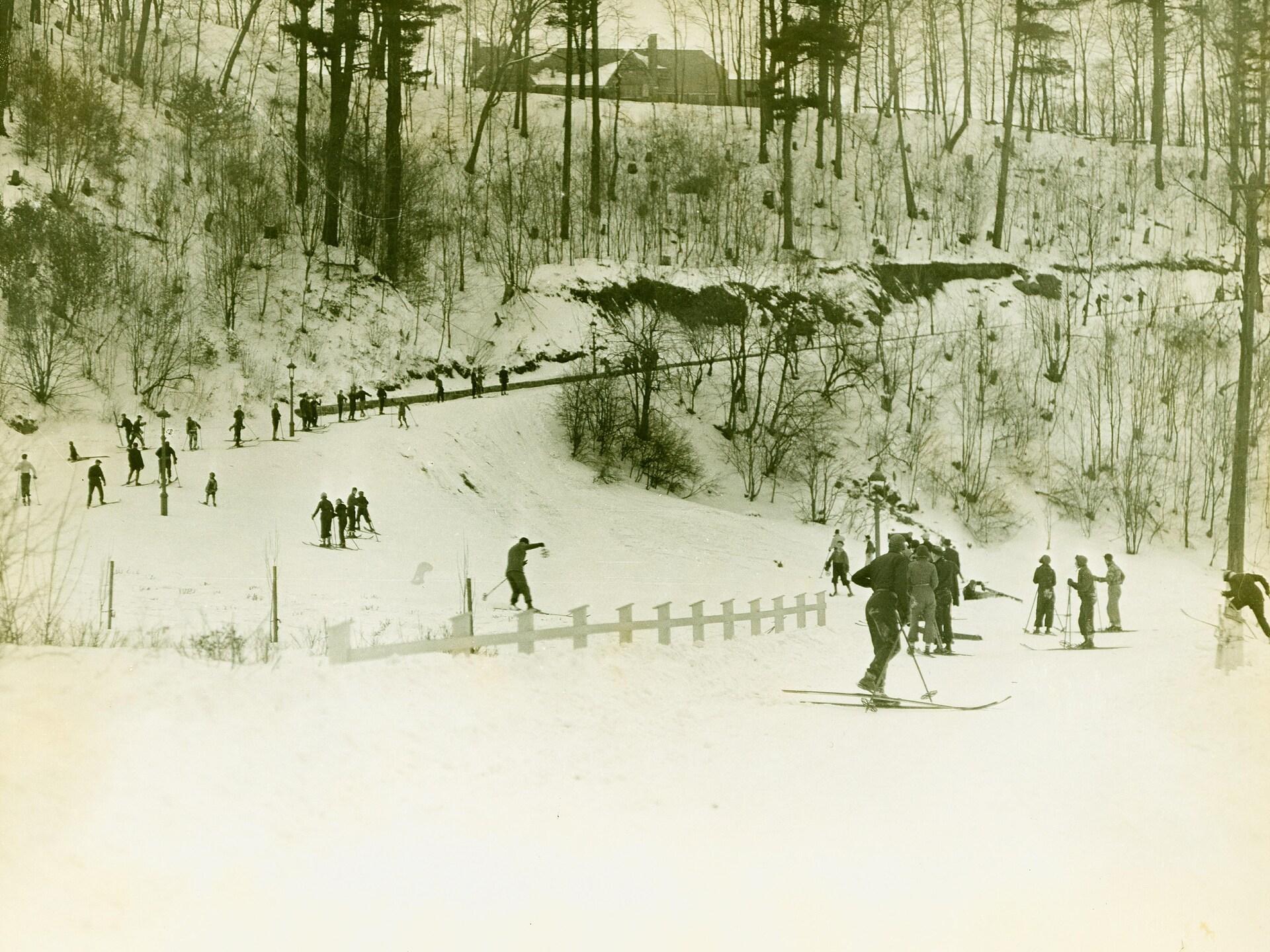 Des skieurs des années 1930 sillonnent la côte Gilmour et ses méandres boisés, par une nuageuse journée d'hiver.