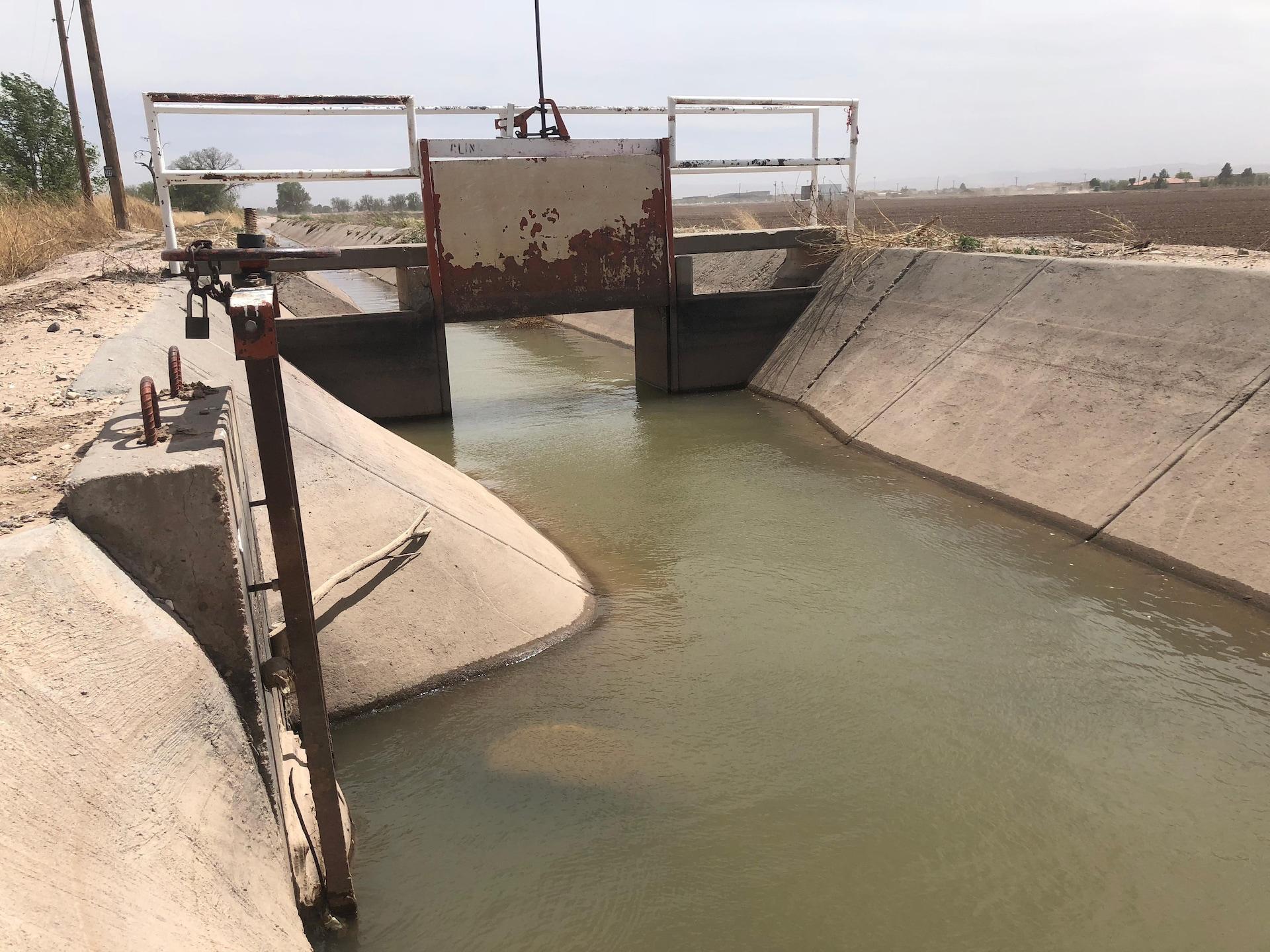Un canal en béton ouvert laisse couler l'eau foncée du Rio Grande.