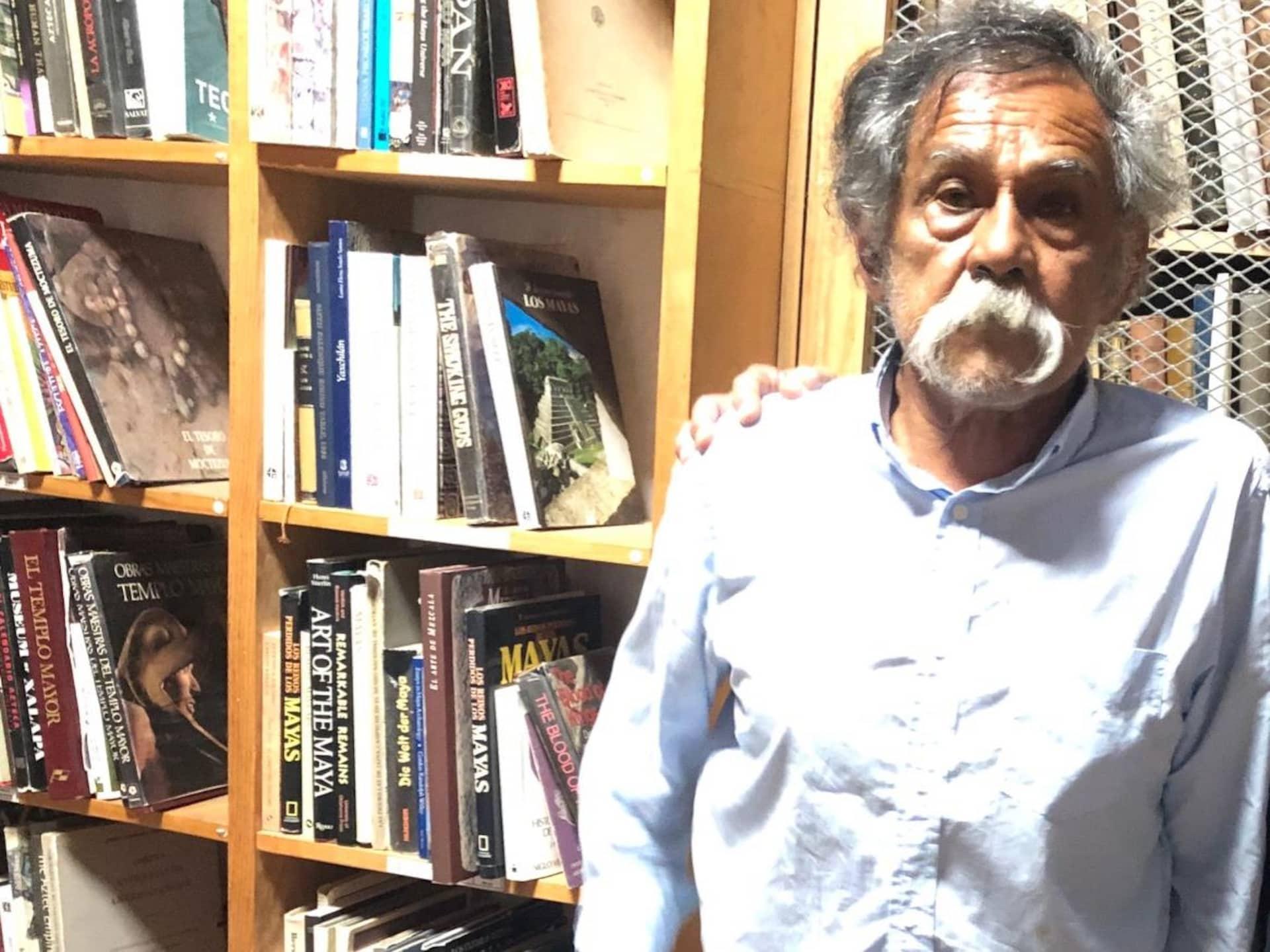 Le peintre se tient debout à côté d'étagères pleines de livres.