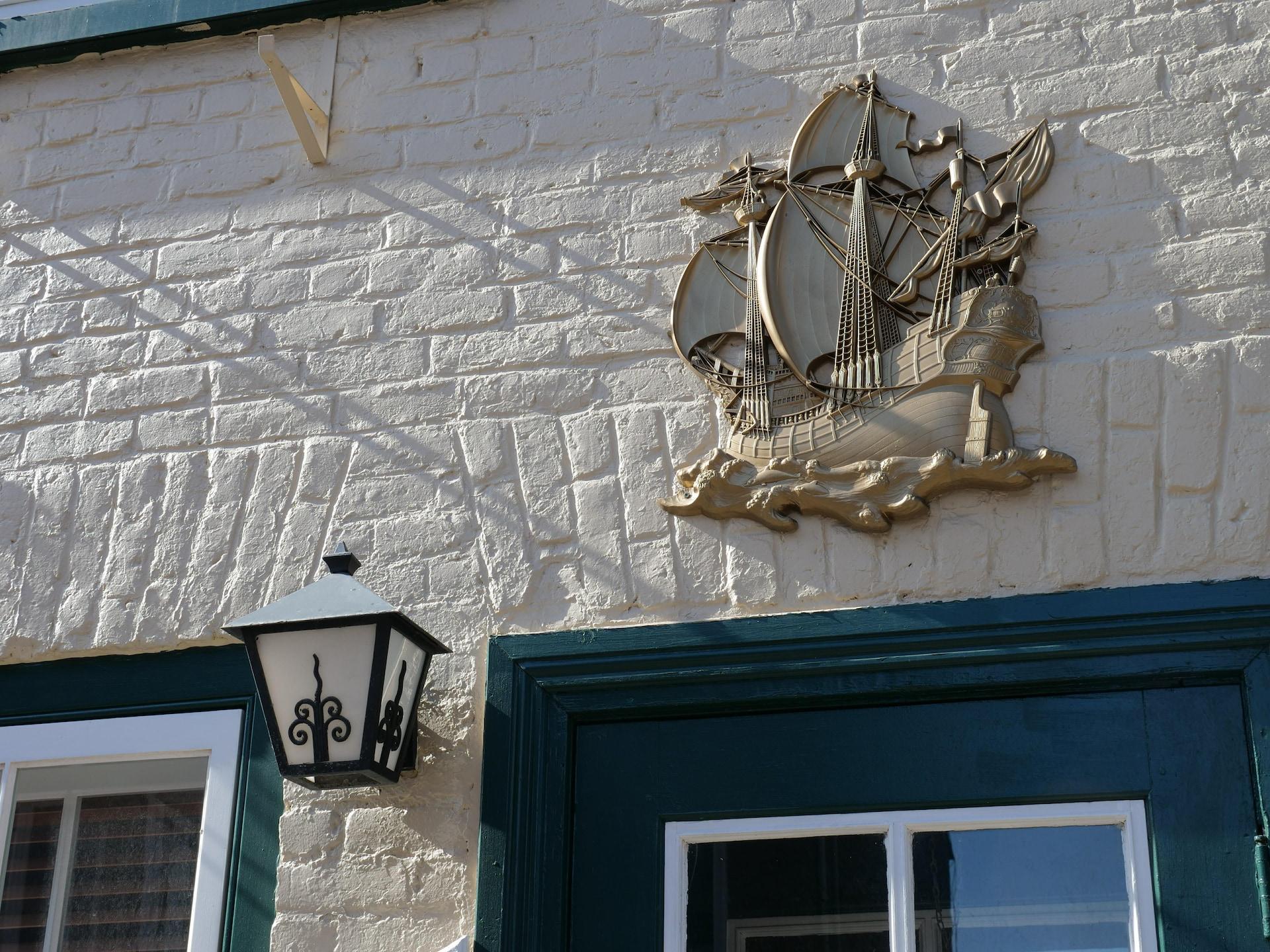 Les décorations maritimes et les lanternes près des portes contribuent au cachet bien particulier de la rue Champlain, comme on le voit sur cette façade de brique rehaussée de détails contrastés.