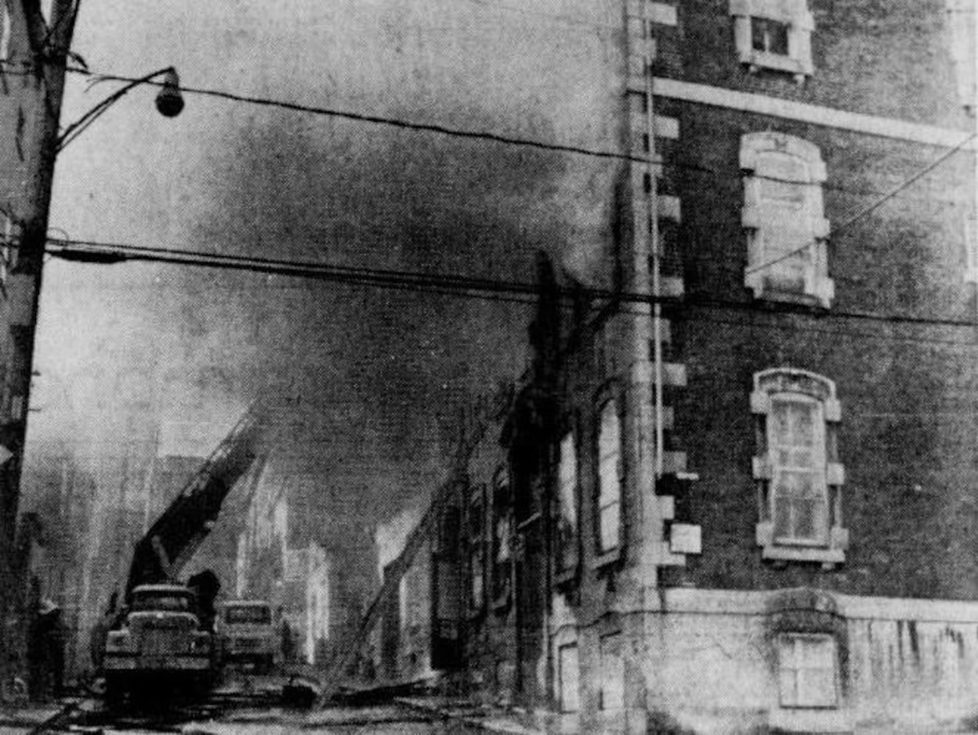 Les pompiers tentent de maîtriser un incendie dans un immeuble de plusieurs étages, sur une image d'archive tirée d'un journal de 1980. On reconnaît l'architecture typique du quartier Saint-Jean-Baptiste, avec ses maisons de briques collées à la rue.