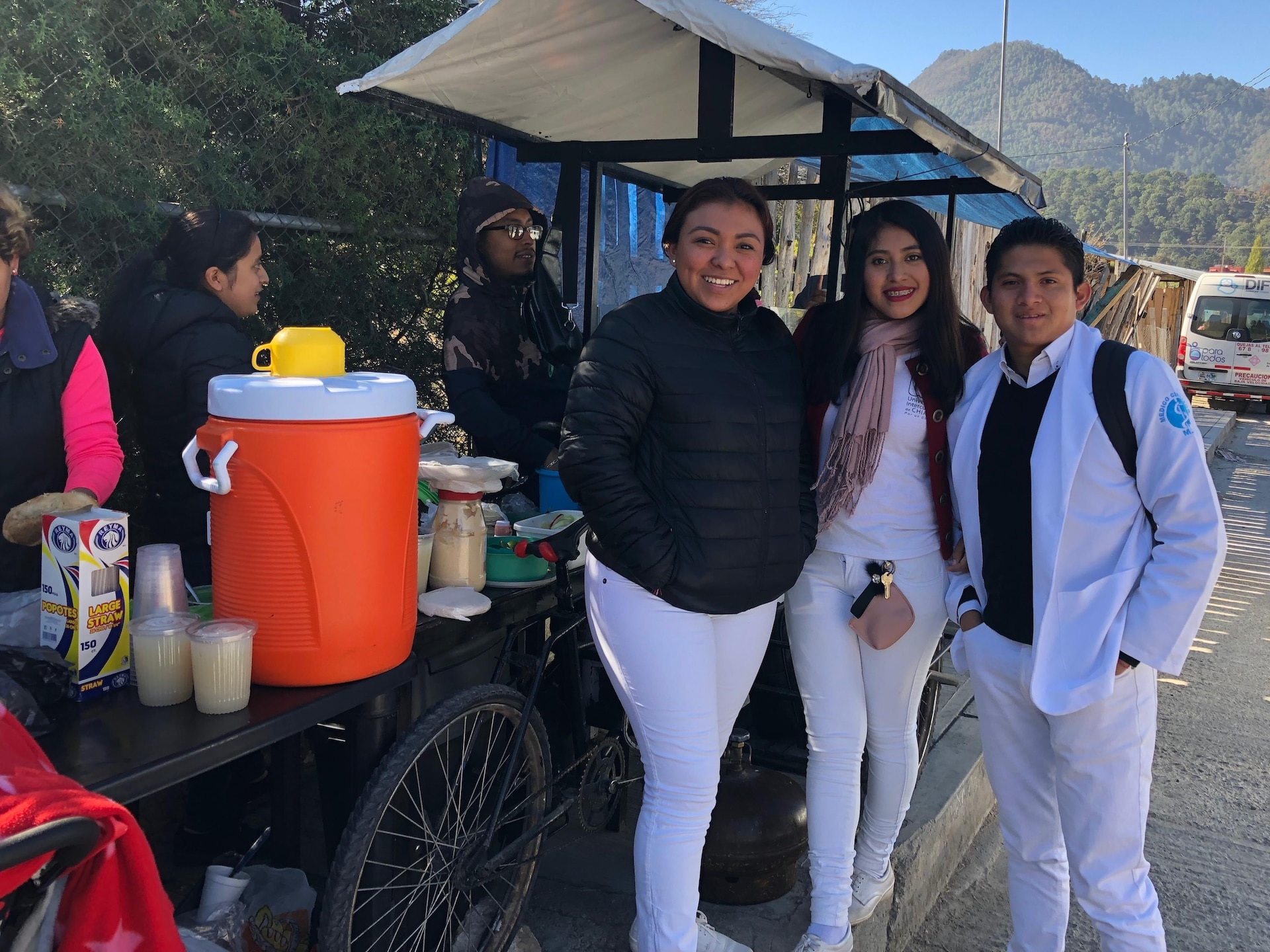 Les deux jeunes filles accompagnées d'un garçon sont devant un étal de nourriture.