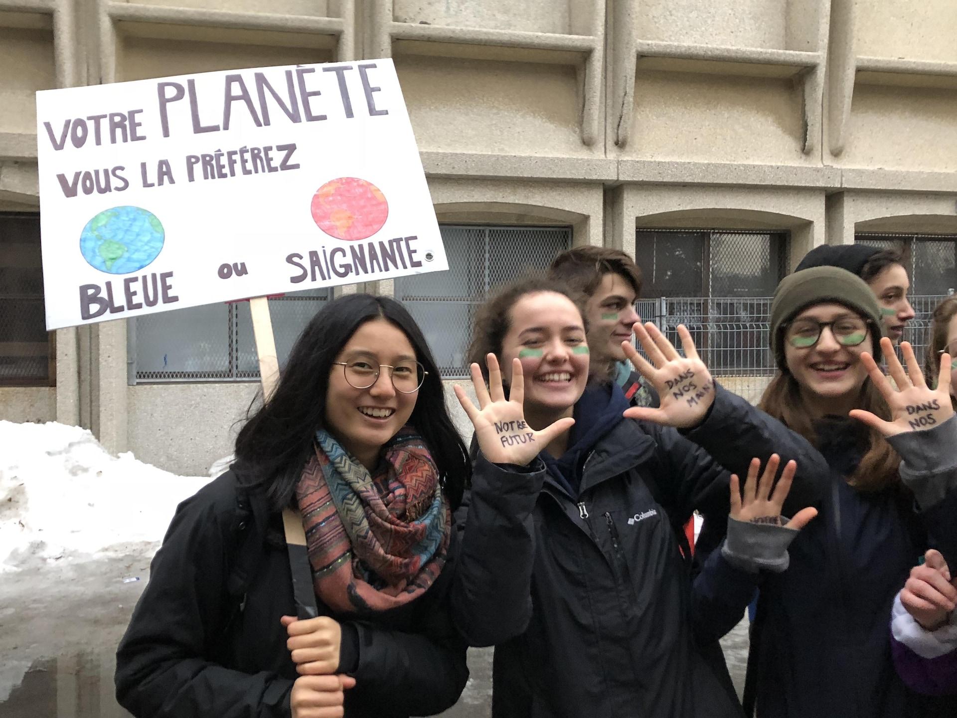 Une jeune fille tient une pancarte demandant : «Votre planète, vous la préférez bleue ou saignante?»