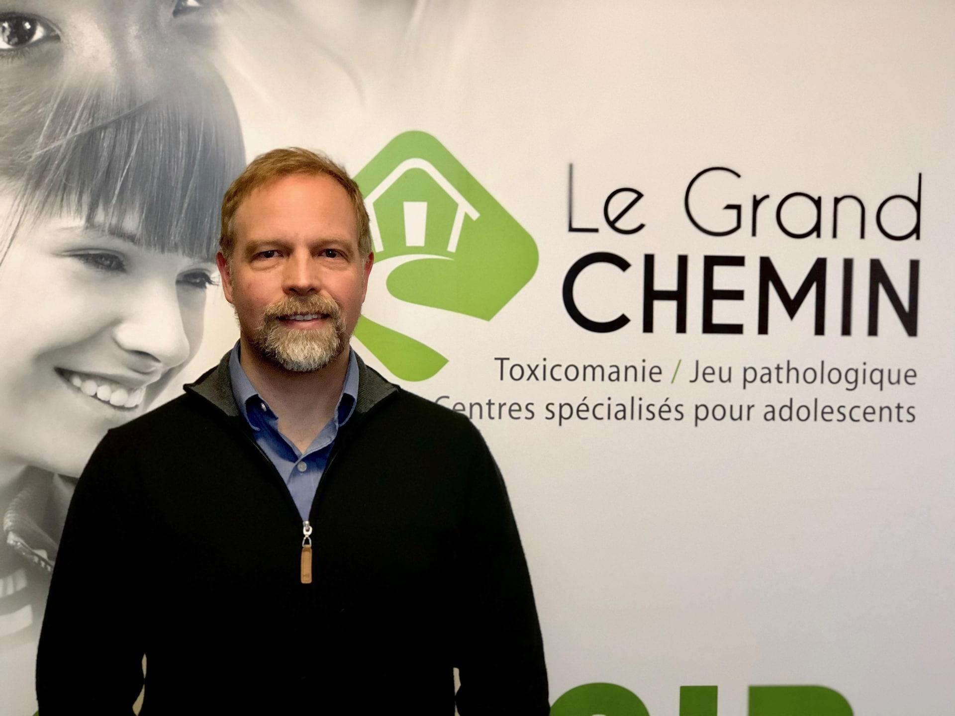 Miguel Therriault pose devant une affiche du centre.
