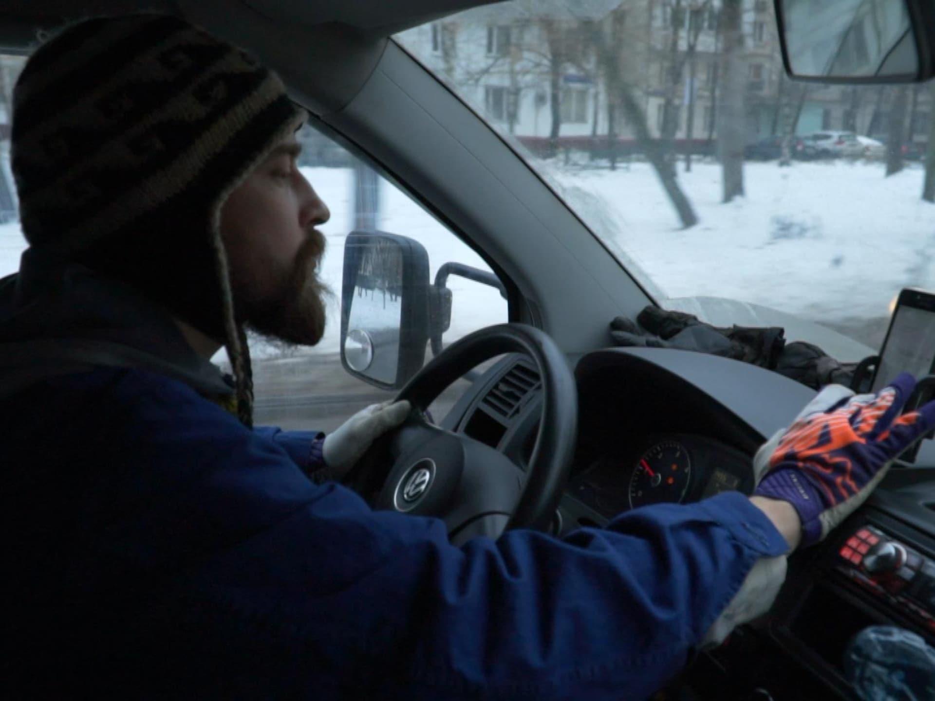 Un homme portant une tuque manipule son téléphone tout en conduisant une voiture dans une rue enneigée.