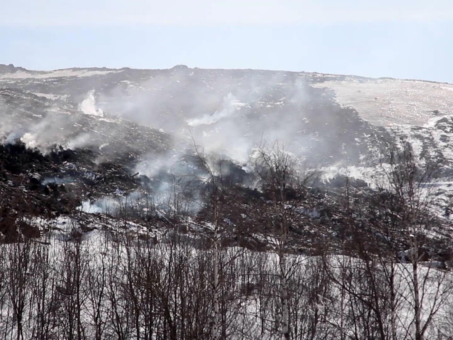 De la fumée se dégage de montagnes de déchets empilés sur une plaine enneigée en banlieue de Moscou.
