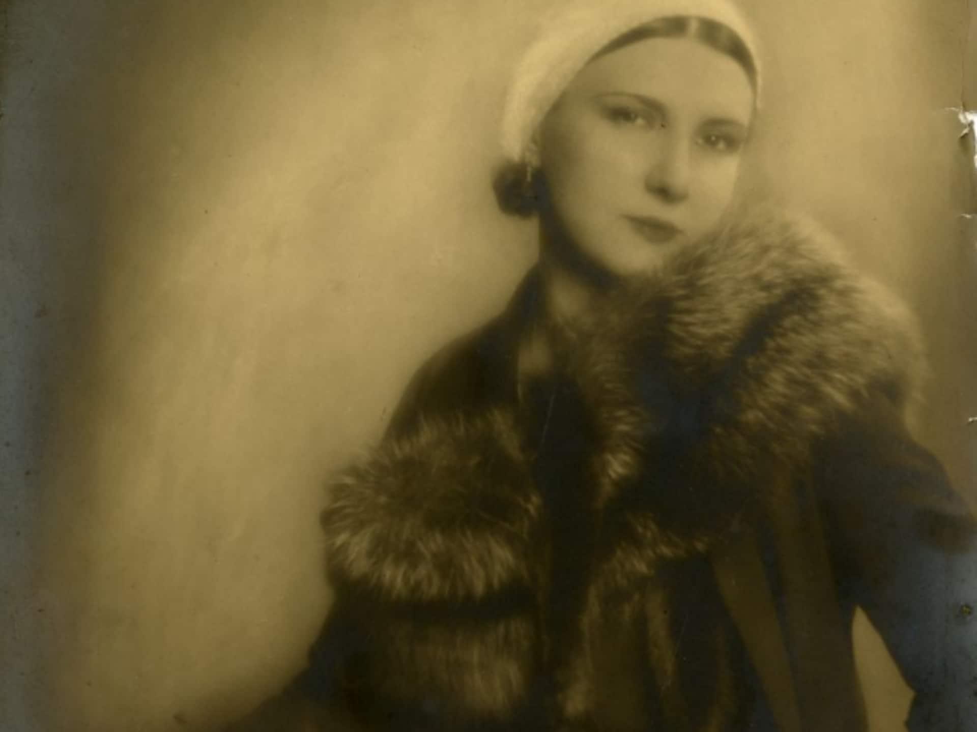 Jeune femme portant une étole de fourrure vers 1920. La pose est élégante et sensuelle, elle porte un élégant chapeau et une grosse bague au doigt, et est soigneusement manucurée et maquillée.