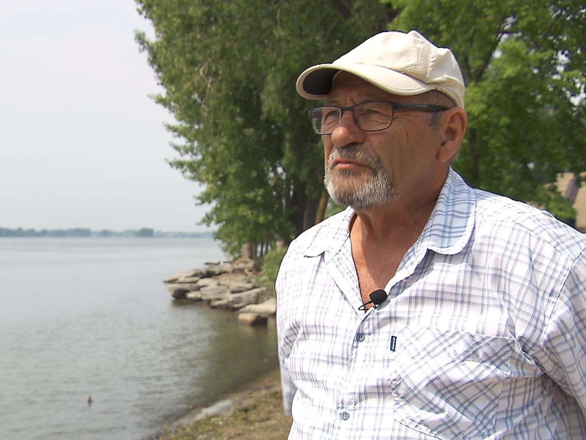 Jacques Durocher se tient debout près de l'eau.