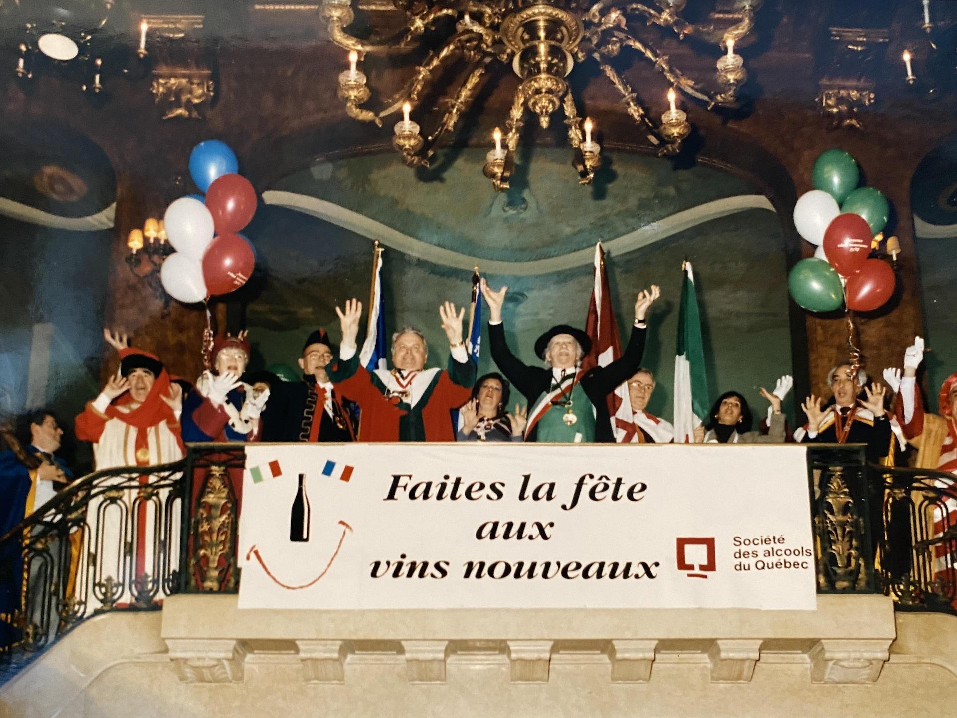 Des gens en costume célèbrent l'arrivée du vin nouveau au Château Frontenac, avec ballons et banderole, dans les années 1980.