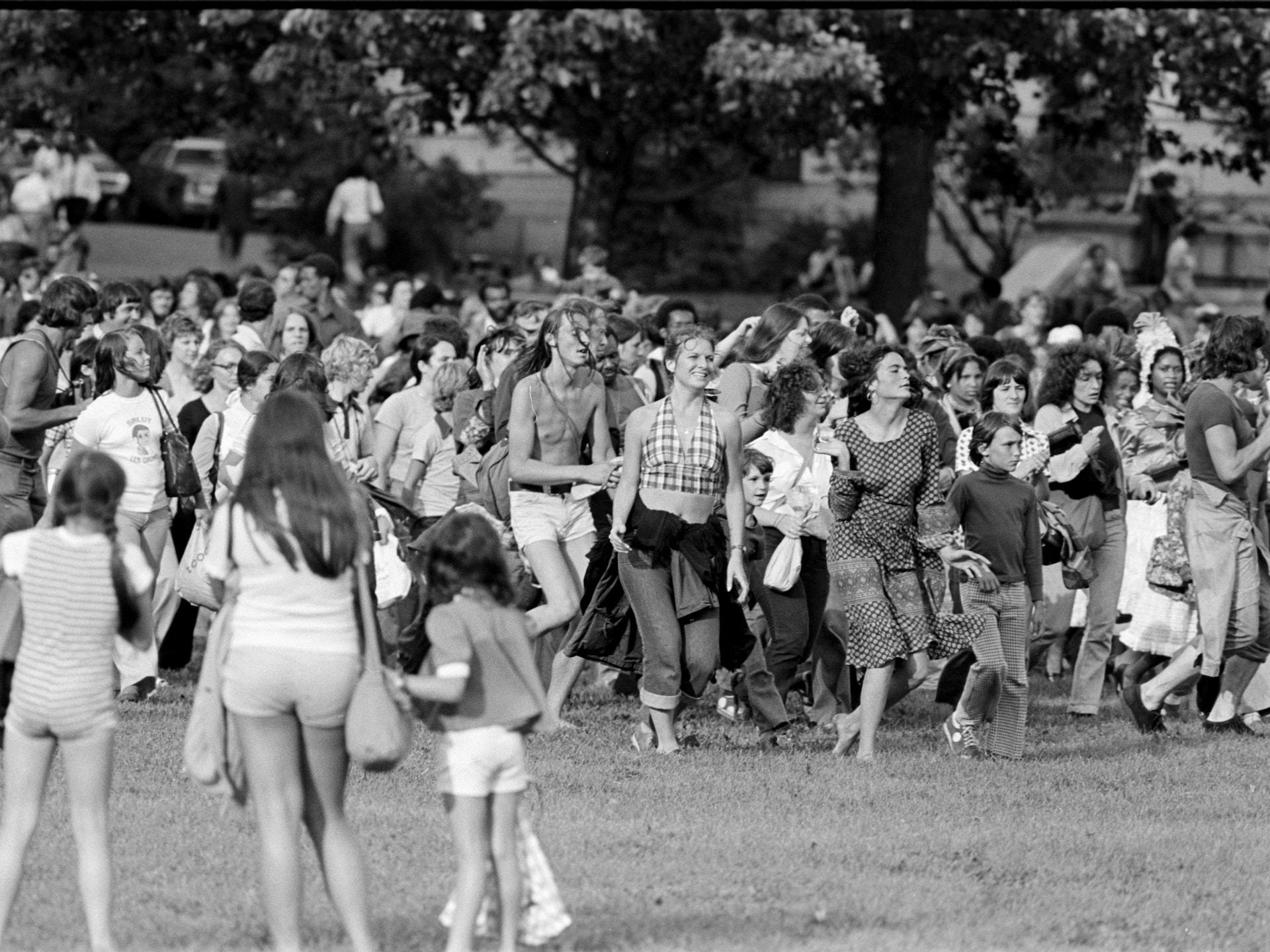 Des marcheurs dont plusieurs ont les yeux mi-clos semblent portés par la musique sur les plaines d'Abraham, sous les yeux de trois jeunes filles en shorts.