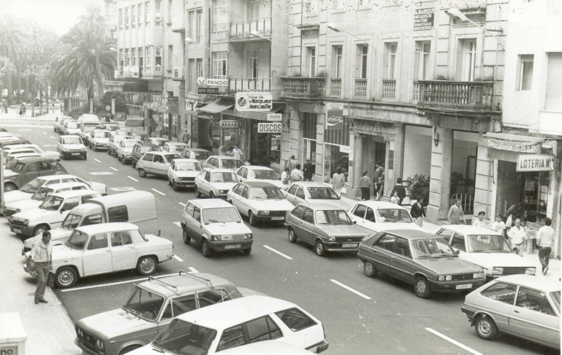 Une photo en noir et blanc d'un centre-ville plein de voitures.