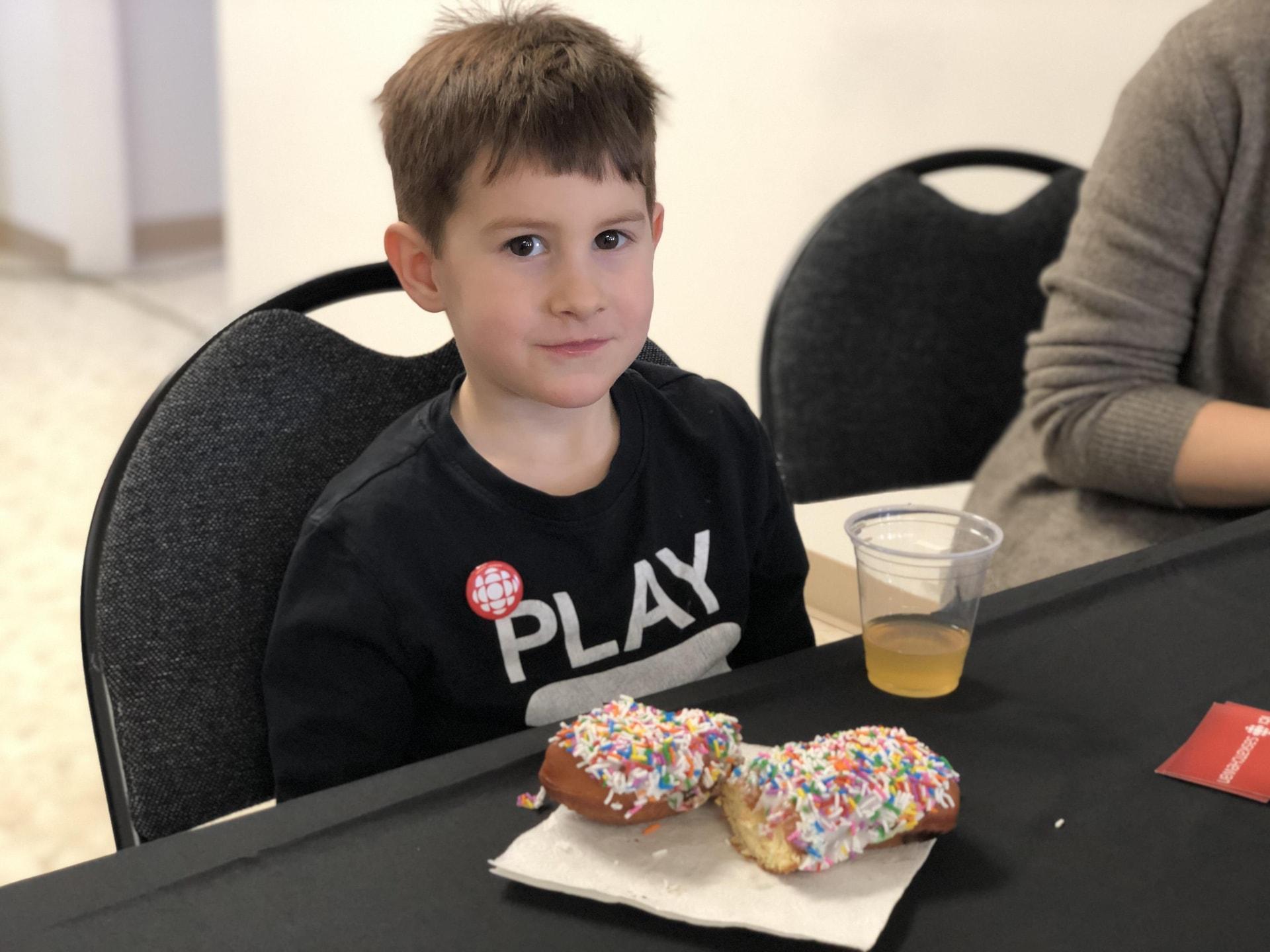 Un jeune homme assis sur une chaise devant des beignets et un verre de jus. Il sourit à la caméra.
