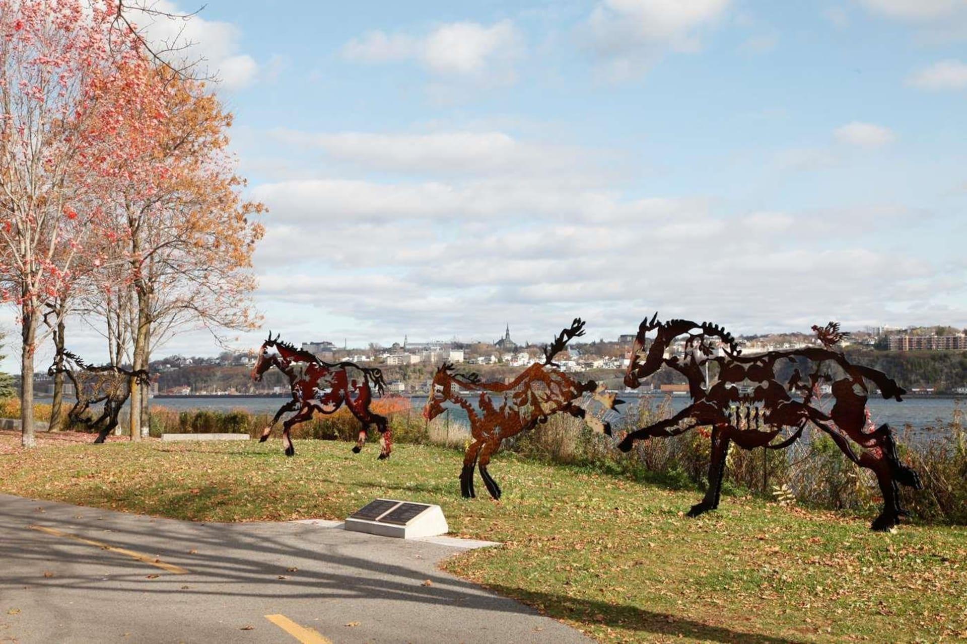 Une sculpture représentant des chevaux en mouvement dans un parc.