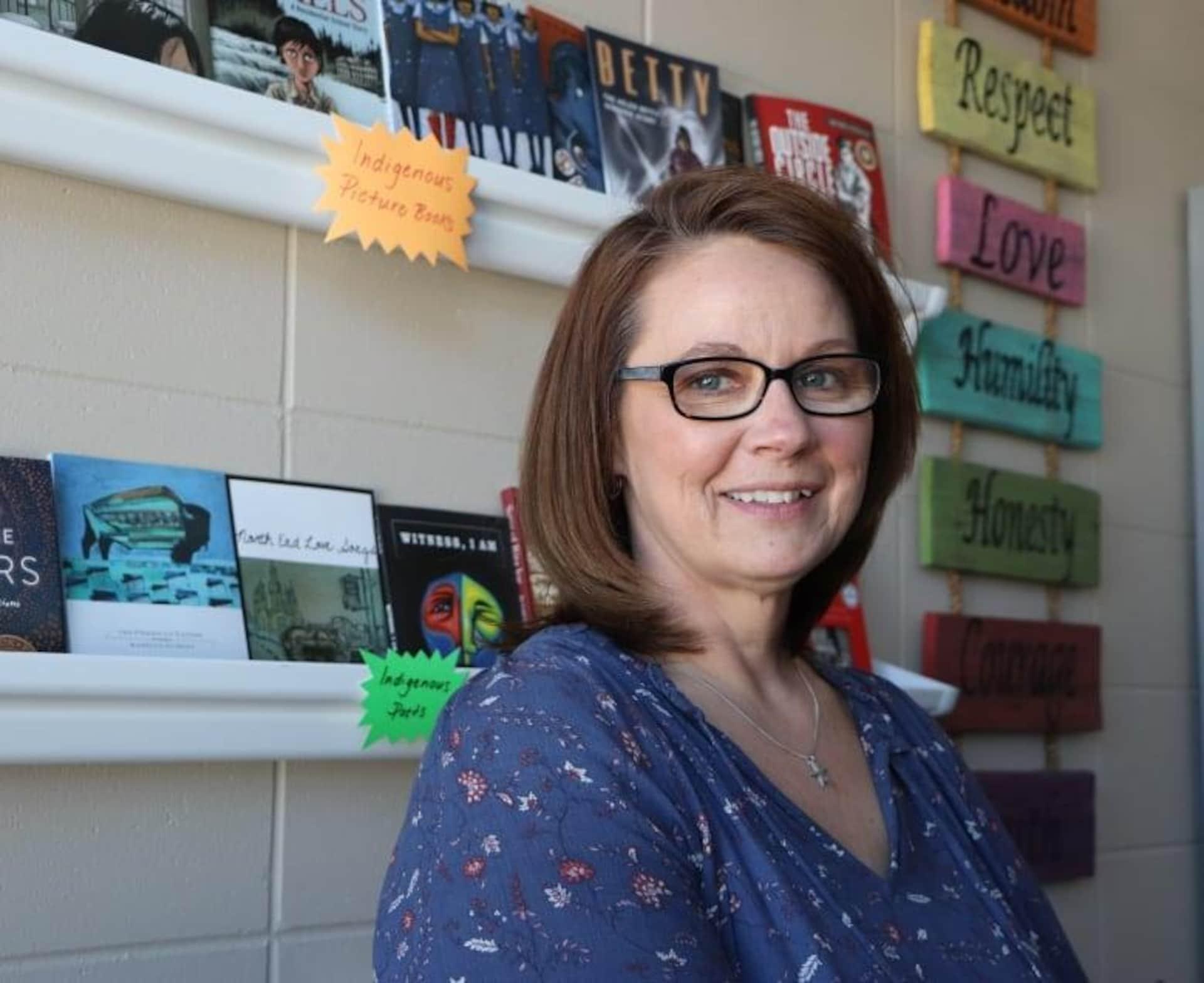 L'enseignante Jennifer Roy regarde la caméra en souriant. Derrière elle, des livres en langue anglaise.