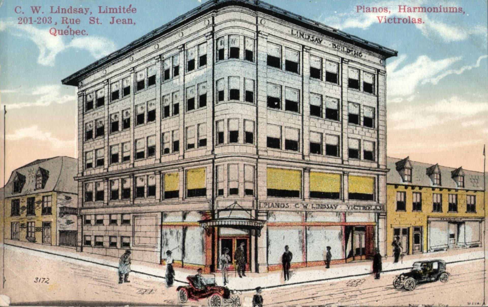 Carte postale colorée montrant un magasin de pianos de la rue Saint-Jean, au tournant des années 1920, avec des marcheurs et des voitures aux alentours.