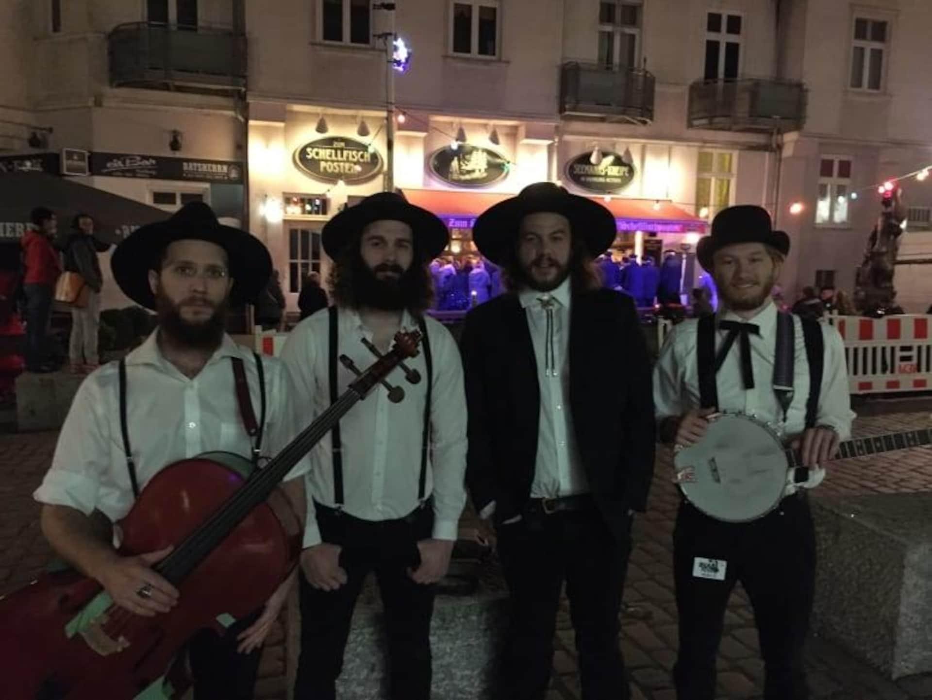 Quatre hommes se tiennent debout côte à côte dans une rue pour prendre une photo. Certains ont un instrument de musique à la main.