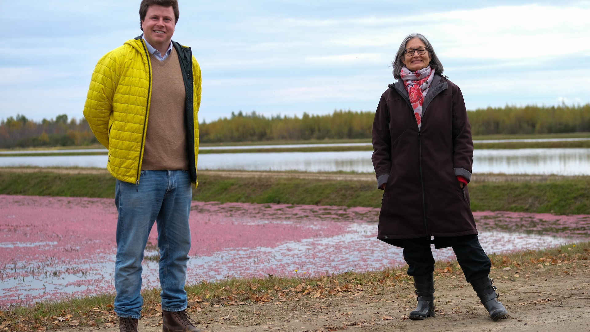 un homme et une femme sourient à la caméra devant un champ de canneberges.