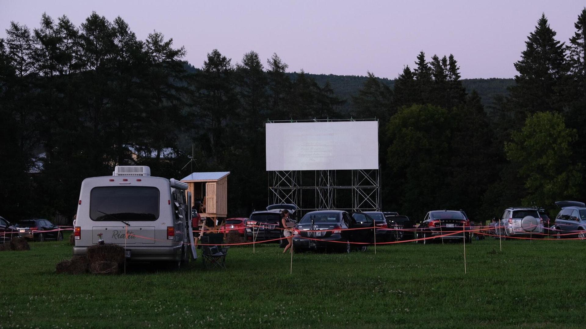 Des véhicules stationnés dans un ciné-parc aménagé sur un terrain gazonné.