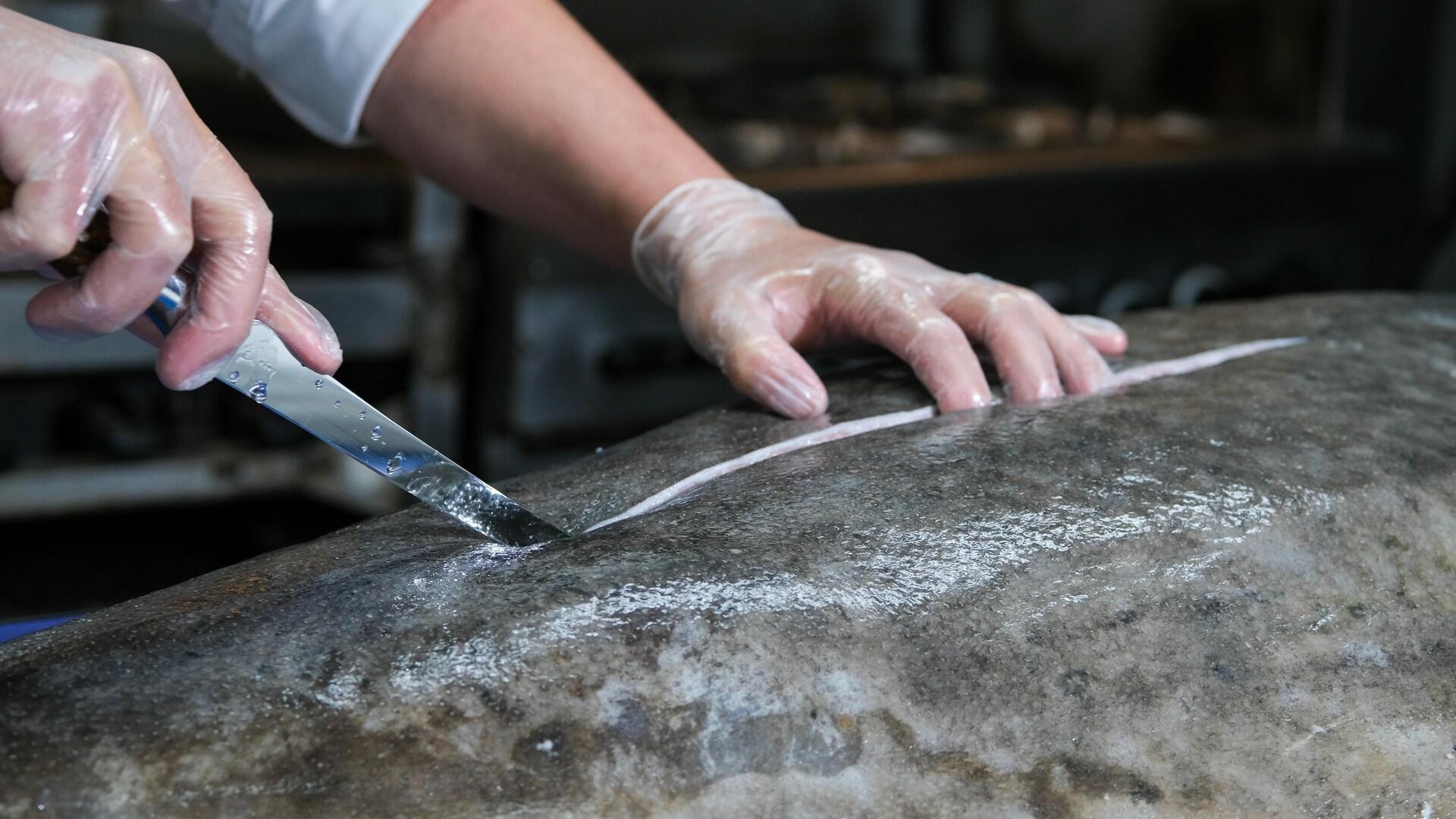 Un couteau coupe la chair du poisson.