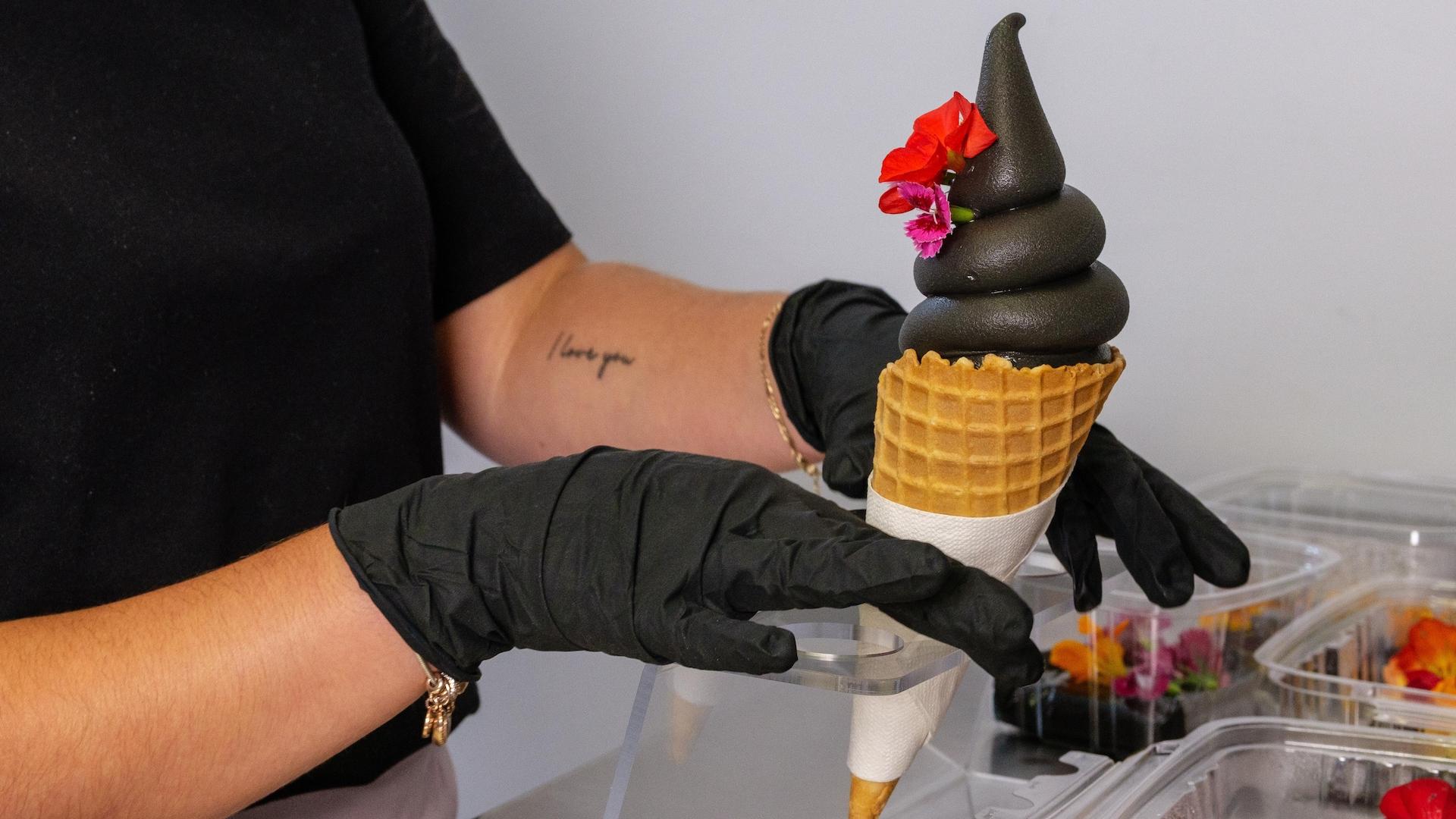 Une jeune femme dépose des fleurs sur un cornet de crème glacée noire.