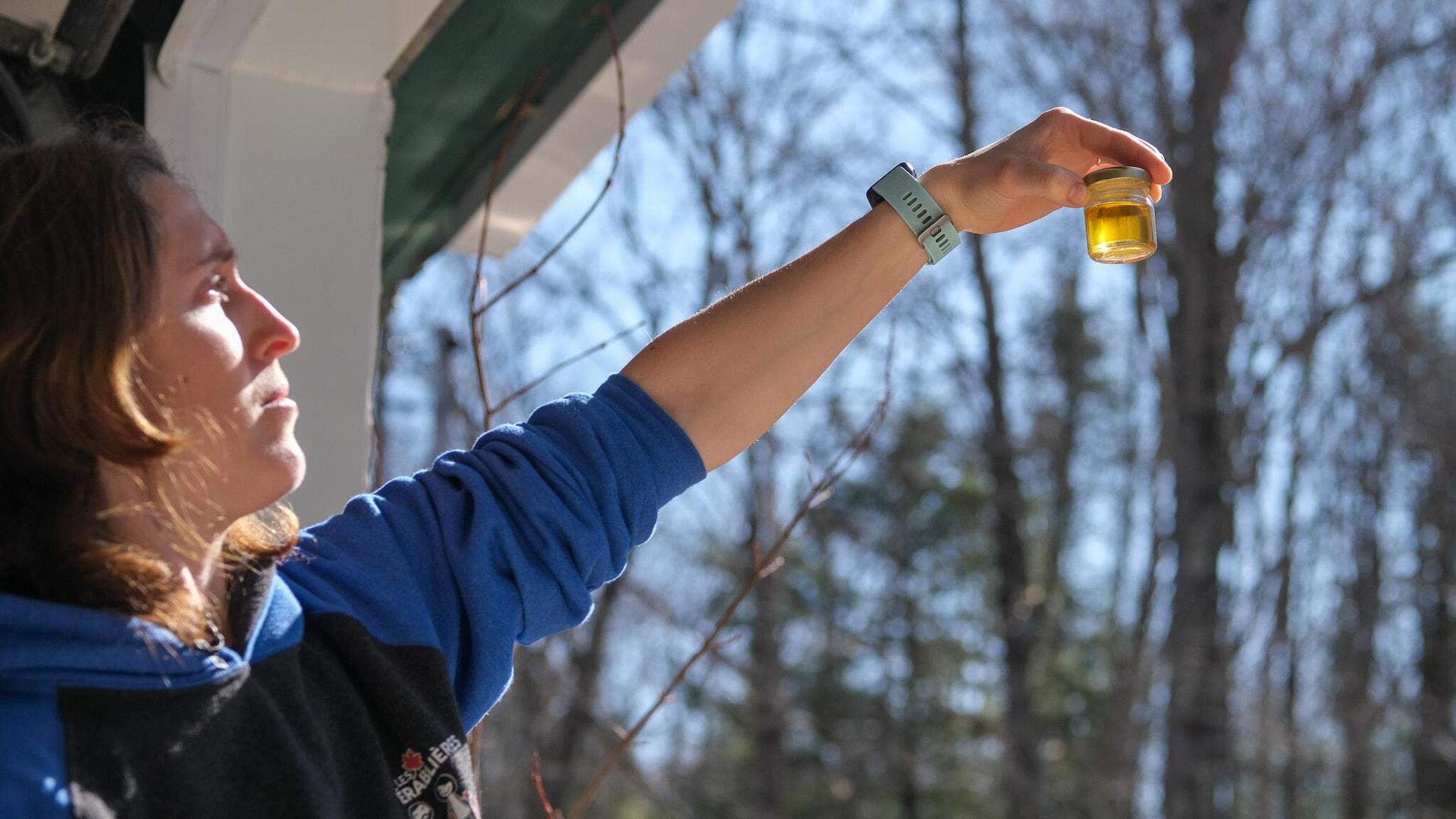 Une femme tient un pot transparent dans lequel il y a du sirop d'érable.