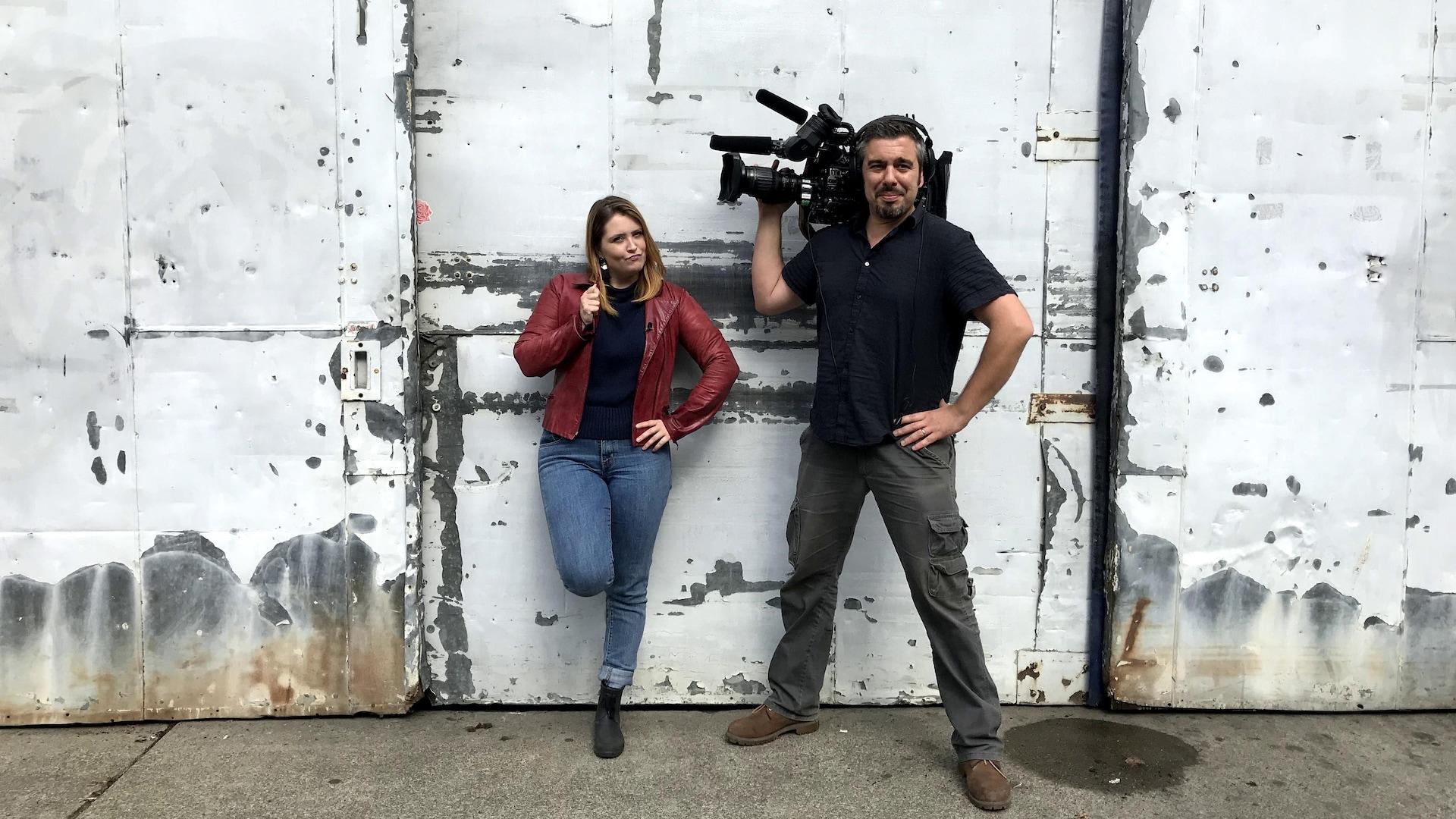 Une femme et un homme avec caméra à l'épaule devant un mur à la peinture délabrée d'une ruelle de Vancouver.