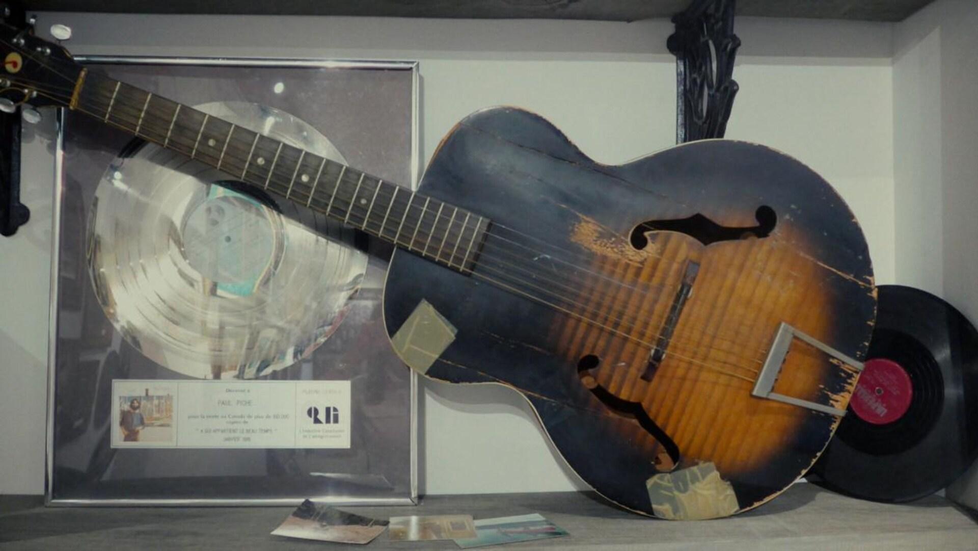 Une vieille guitare, réparée avec du papier adhésif, avec un disque hommage de Paul Piché.