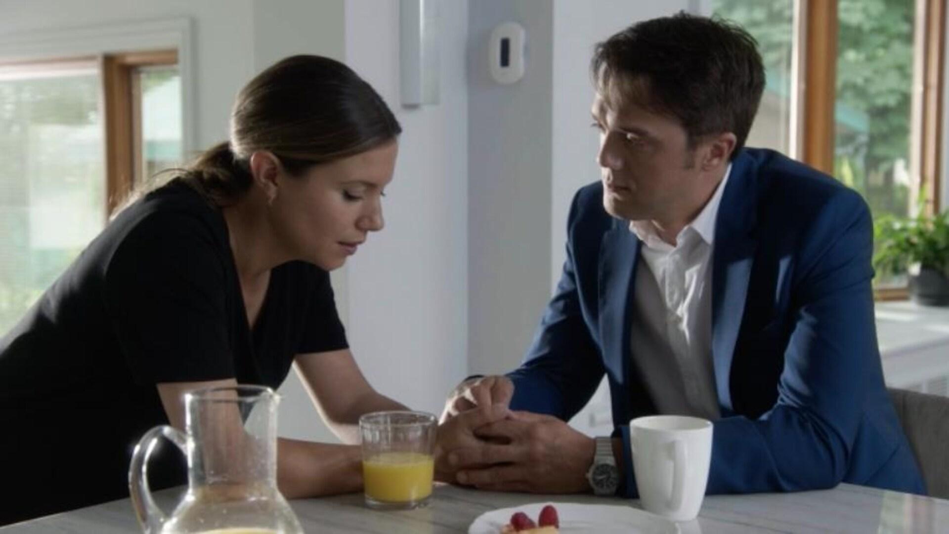 Dans leur cuisine, les deux personnages parlent en se tenant les mains.