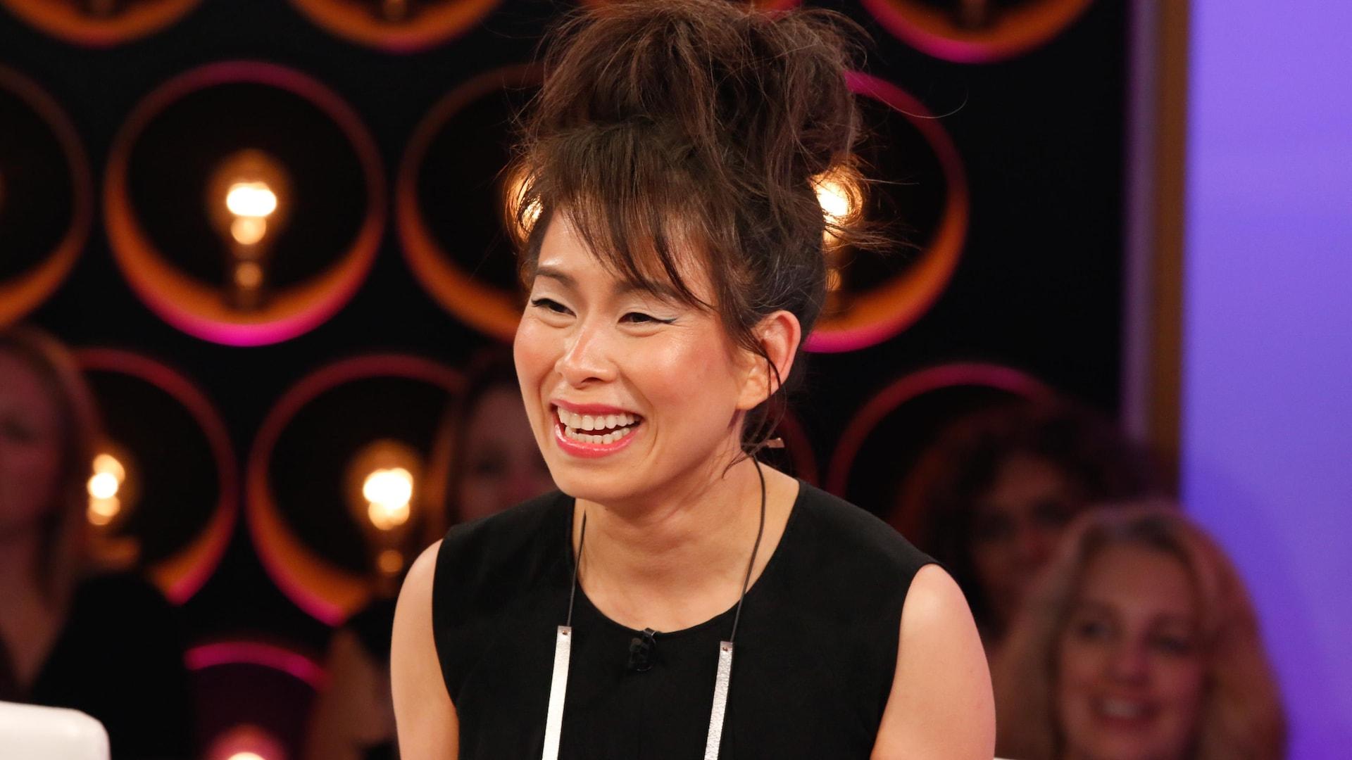 Habillée d'une robe noire, l'écrivaine d'origine vietnamienne montre son plus beau sourire.