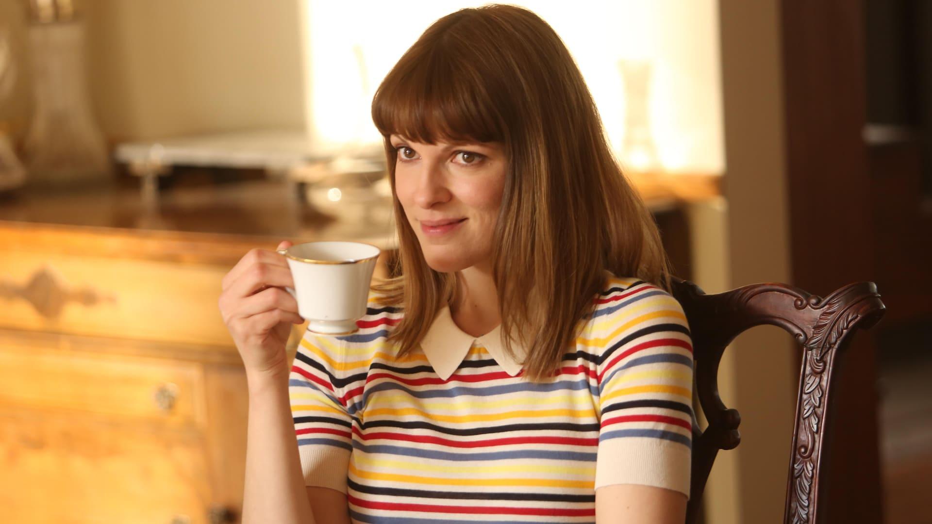 Elle boit du thé. Elle porte un chandail rayé en couleur.