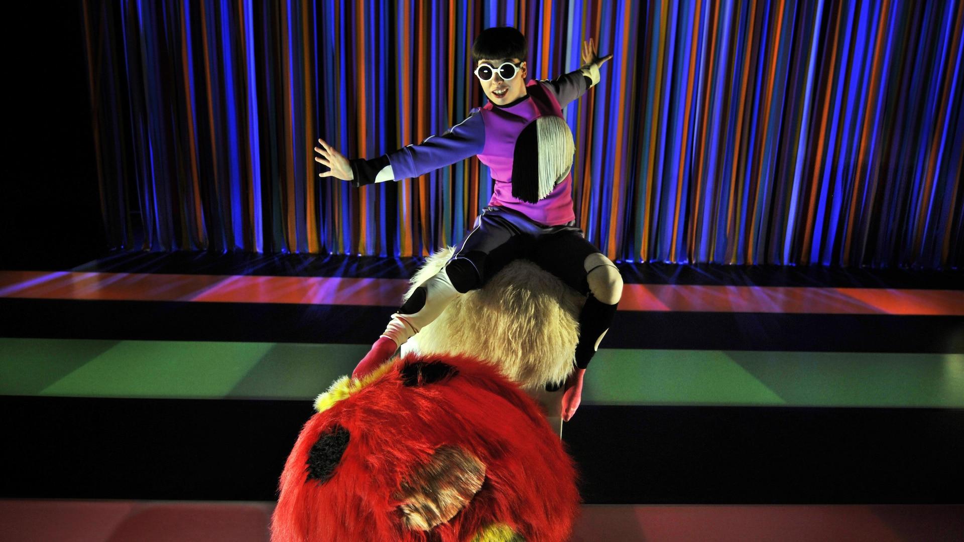 Une acrobate est assise, bras tendus, sur un gros rouleau de fourrure rouge et jaune.