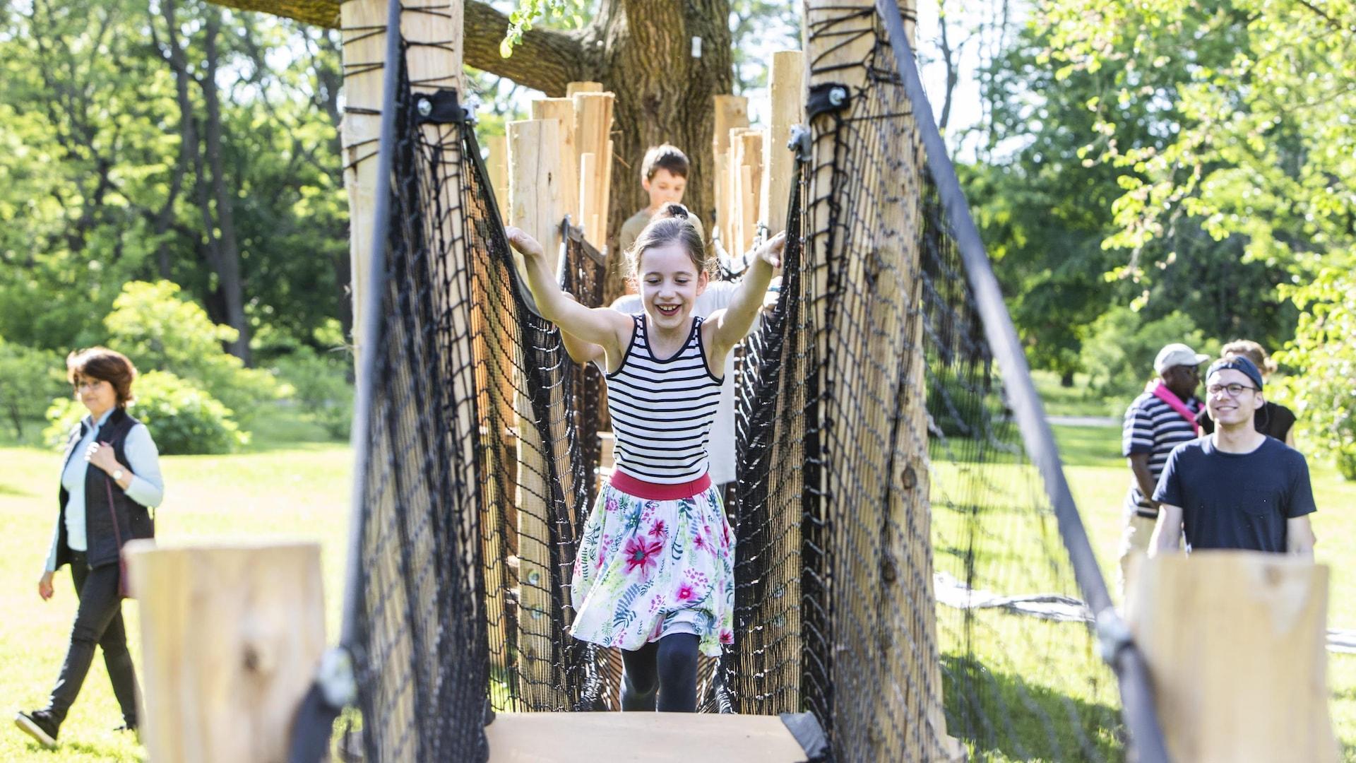Des enfants traversent un pont suspendu.