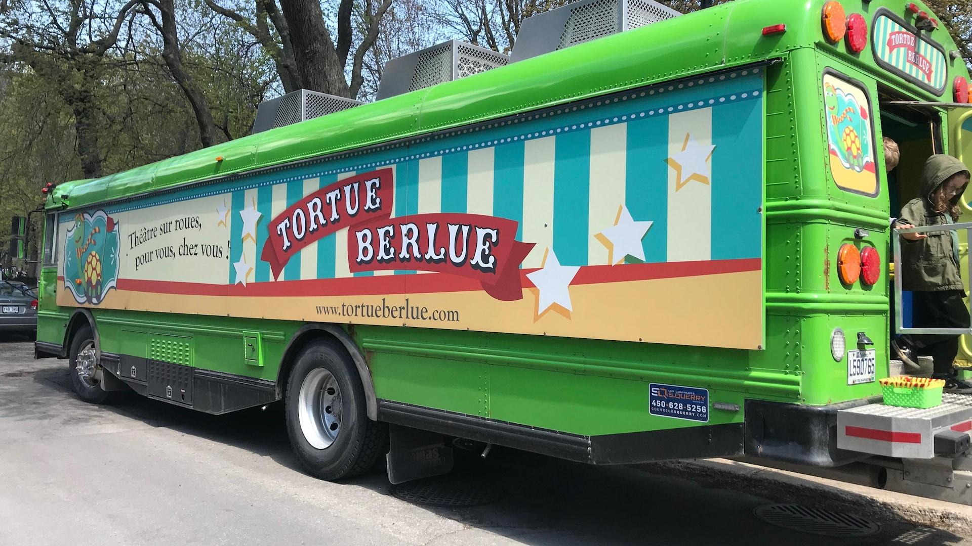 L'autobus du théâtre Tortue Berlue est stationné à côté d'un parc.