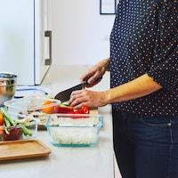 Une femme qui tranche des légumes sur un plan de travail avec différents plats réutilisables en verre.