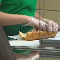 Une femme place de la viande dans un sandwich.
