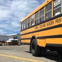 Un autobus scolaire avec une école à l'arrière.