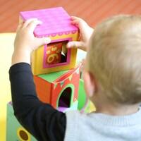 Un enfant de dos joue avec des blocs dans une garderie.