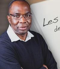 Jean-Marie Yambayamba avec un air sérieux et les bras croisés.