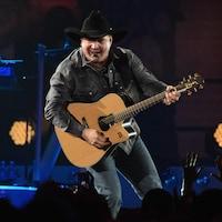 Garth Brooks, sur scène, chante avec une guitare à la main pendant un spectacle.