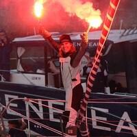 Une femme sourit sur son bateau en tenant deux fumigènes.