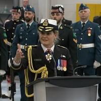 Julie Payette, en uniforme, parle au podium alors qu'on voit des militaires à l'arrière.