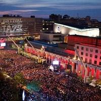 Vue aérienne d'une foule sur la place des Festivals, par un soir d'été.